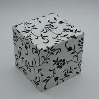 Caja en forma de cubo y apertura de concha. Exterior en papel artesano decorado, cajones e interior en Geltex. Artículo hecho a mano.